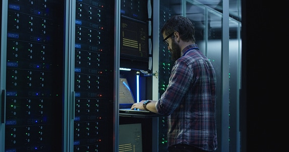 Adult bearded system administrator in glasses walks over to the server rack and opens the rack door in the server room and makes the hardware settings using a laptop.